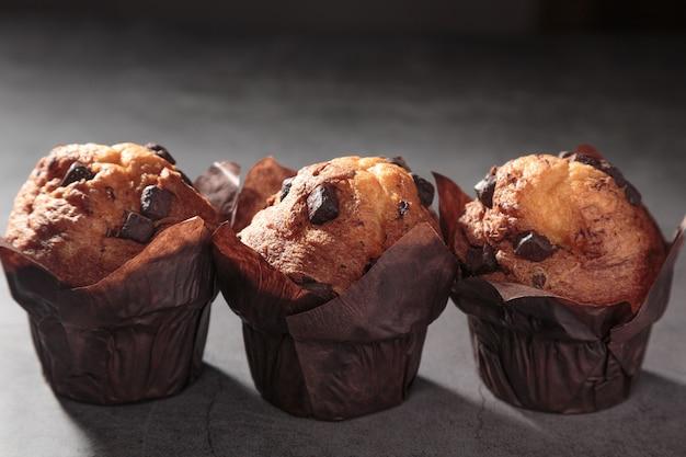 Drie chocolademuffins op een donkere achtergrond.