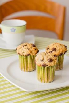 Drie chocoladeschilfermuffins op wit bord en groen gestreept tafelkleed bij ontbijt