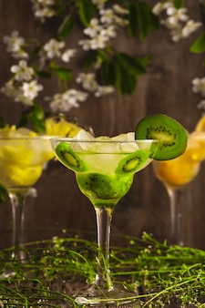 Drie cocktails met ananas, sinaasappel en kiwi