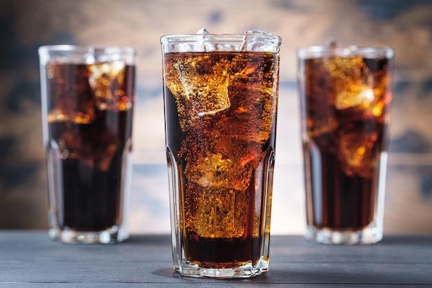 Drie colaglas met ijsblokjes en bubbels