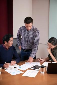 Drie collega's bespreken bedrijfsrapport dat statistische gegevens onderzoekt