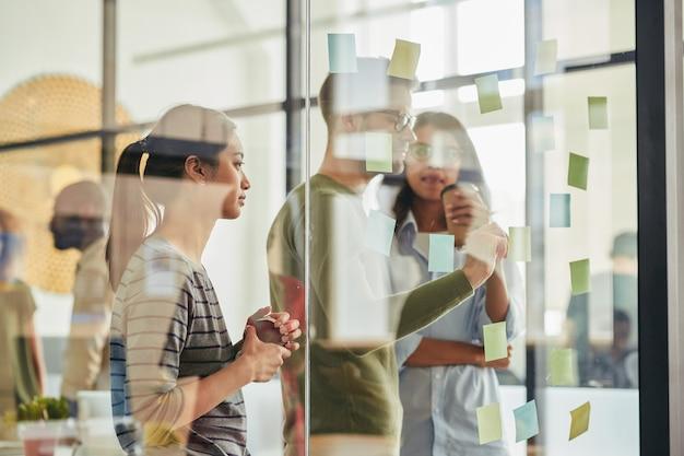 Drie collega's in gesprek achter glazen wand