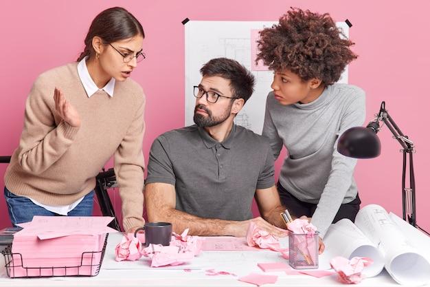 Drie collega's werken productief samen, creëren een nieuwe planning van het kantoor, bespreken schetsen en geven elkaar advies, verbeteren het ontwerpproject communiceren tijdens een brainstormvergadering