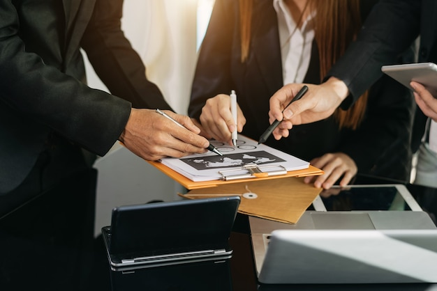 Drie collega'szaken die gegevens en digitale tablet en computerlaptop met steekproefmateriaal op bureau in bureau als concept bespreken