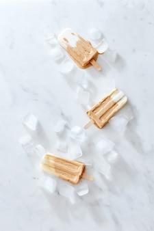 Drie creme brulee koffie-ijsjes op een houten stok over marmeren achtergrond, bovenaanzicht. gezond zomerdessert