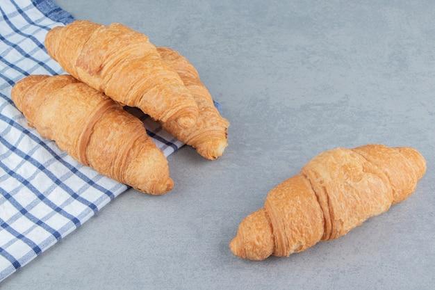 Drie croissants gestapeld op de handdoek met een croissant op de marmeren achtergrond. hoge kwaliteit foto