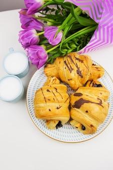 Drie croissants, twee kopjes koffie op tafel en een bos prachtige tulpen