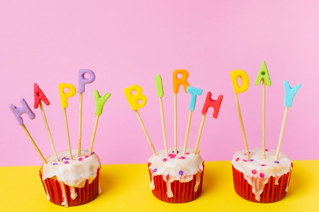 Drie cupcakes met gelukkige verjaardag belettering