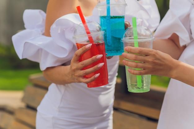 Drie dames juichen met smakelijke nectars met ijsblokjes met zwarte rietjes palmen decoratie in zwembad transparant schoon helder blauw water zon schijnt gladde gebruinde huid zorgeloze feestelijke modus