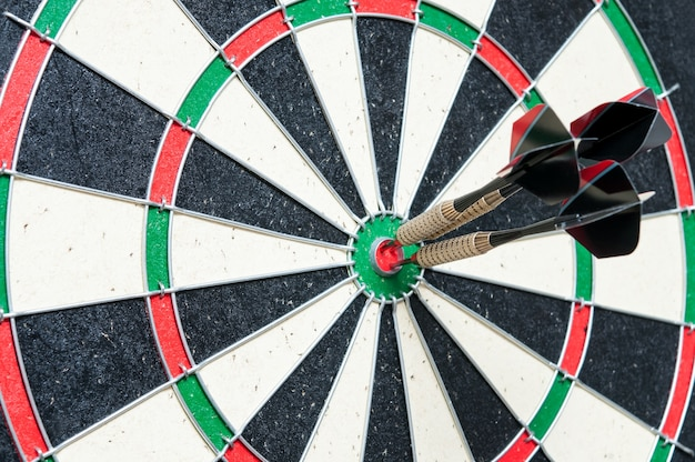 Drie darts in het midden van het dartbord