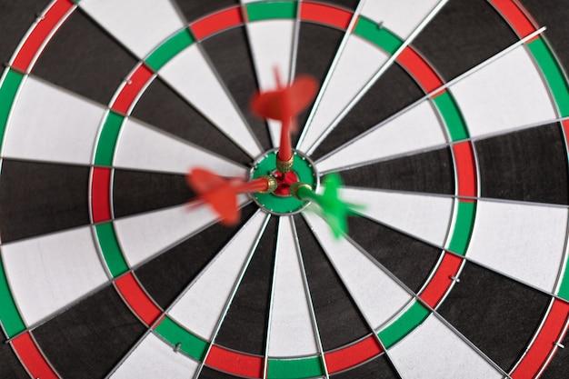 Drie darts raken rood doel op het doel juist close-up