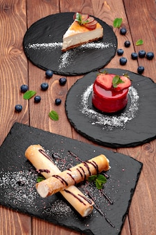 Drie desserts geserveerd op zwarte platen op houten tafelblad