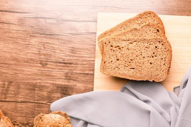Drie donkere sneetjes brood op een houten tafel