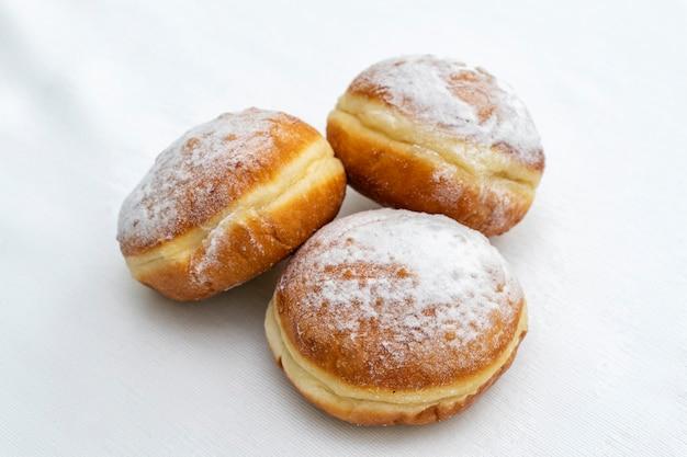Drie donuts bestrooid met poedersuiker op een lichte ondergrond