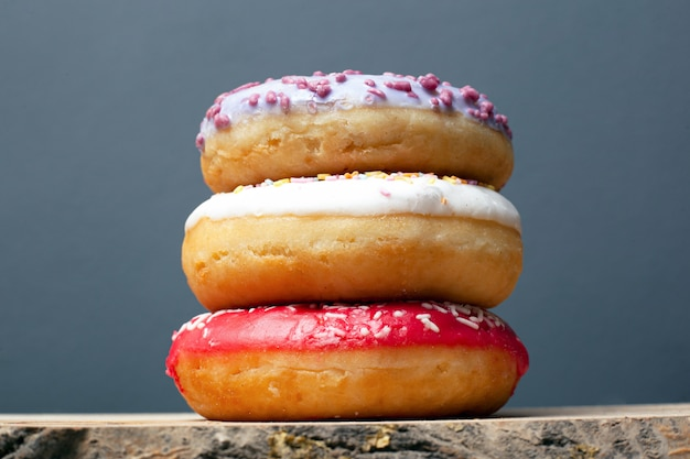 Drie donuts met gekleurde glans van violet rood en wit met poeder staan bovenop elkaar op een tribune op een grijze close-up als achtergrond.