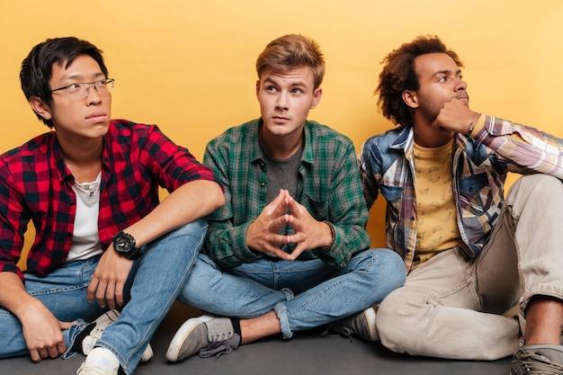Drie doordachte knappe jonge mannen vrienden zitten en denken over gele achtergrond