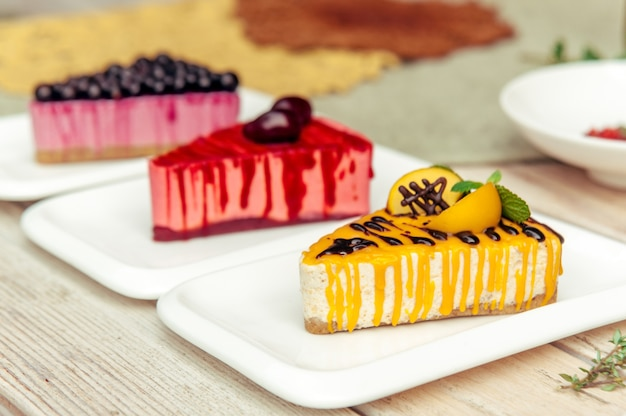Drie driehoekige stukjes cake met abrikozenpruim en bes op houten rustieke tafel