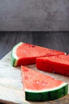 Drie driehoekige stukjes watermeloen op een moederbord en rustieke achtergrond