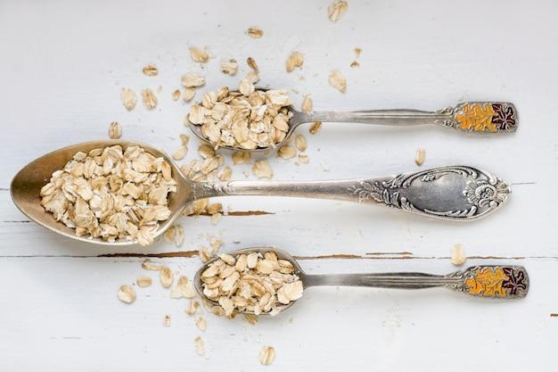 Drie eetlepels havermout liggend op een witte houten gezonde voeding.