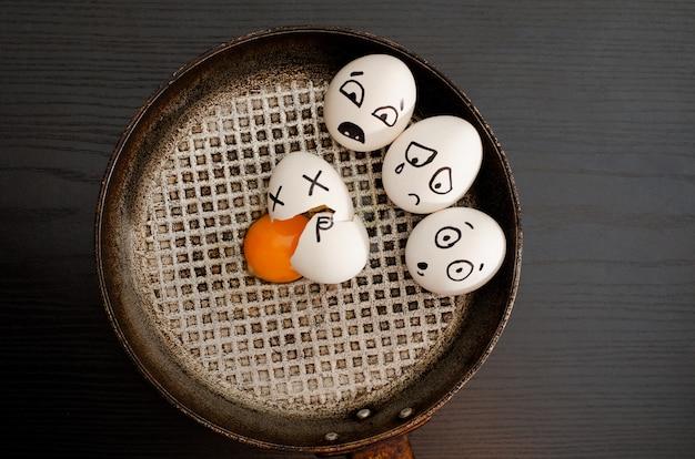 Drie eieren beschilderd met emoties, gebroken ei in het midden van de pan, zwarte tafel, ruimte voor tekst