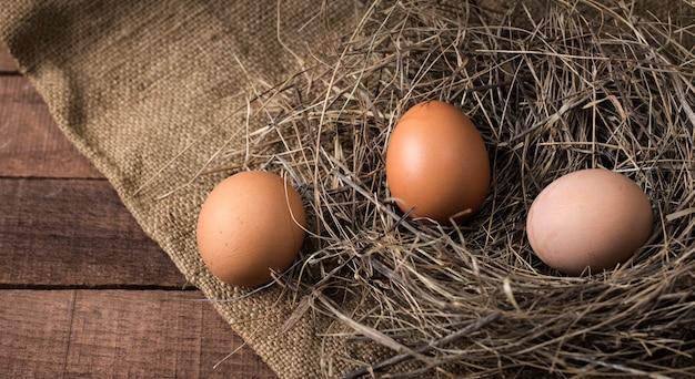 Drie eieren in een nest van hooi op een achtergrond van jute op een houten oppervlak, bovenaanzicht.