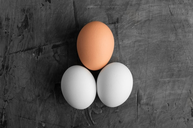 Drie eieren, twee wit en een bruin op een zwarte achtergrond. kopieer ruimte