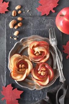 Drie eigengemaakt bladerdeeg met roosvormige appelplakken op metaalplaat