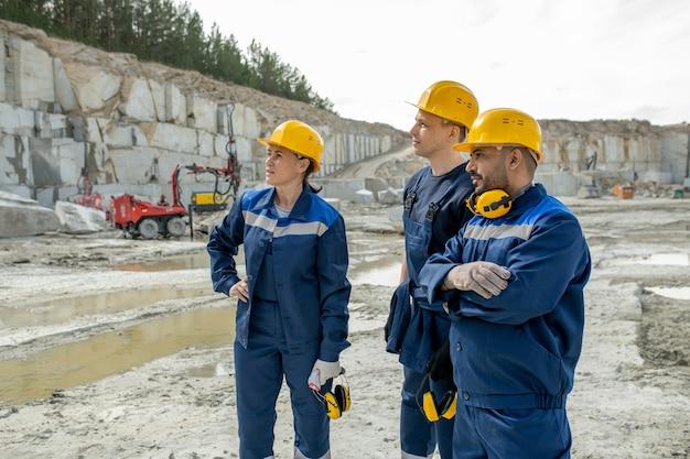 Drie eigentijdse bouwers in uniform en veiligheidshelmen op de werkplek