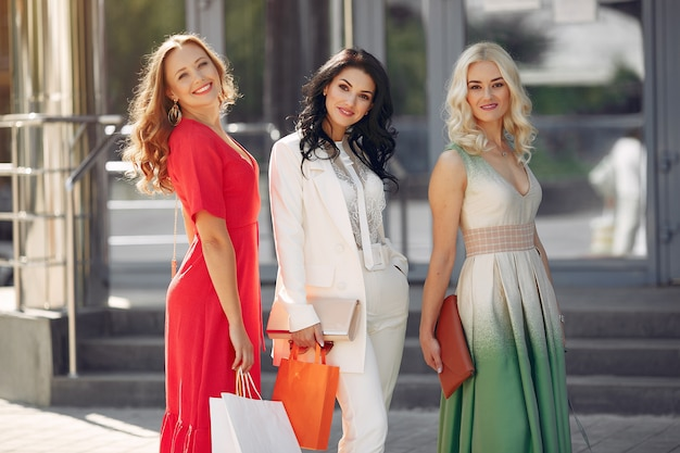 Drie elegante vrouwen met boodschappentassen in een stad