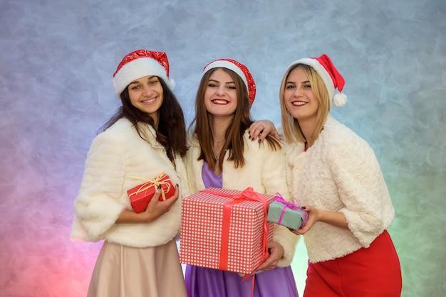 Drie elegante vrouwen met geschenkdozen. gelukkig nieuwjaarsfeest