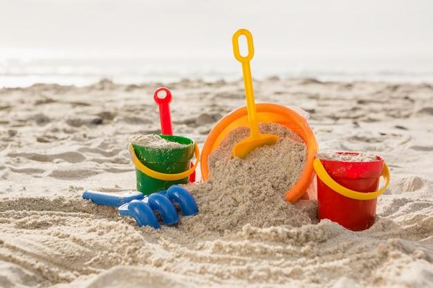 Drie emmers met zand en een spade op het strand