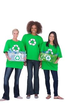 Drie enivromental activisten met twee holdingsdozen van recyclables