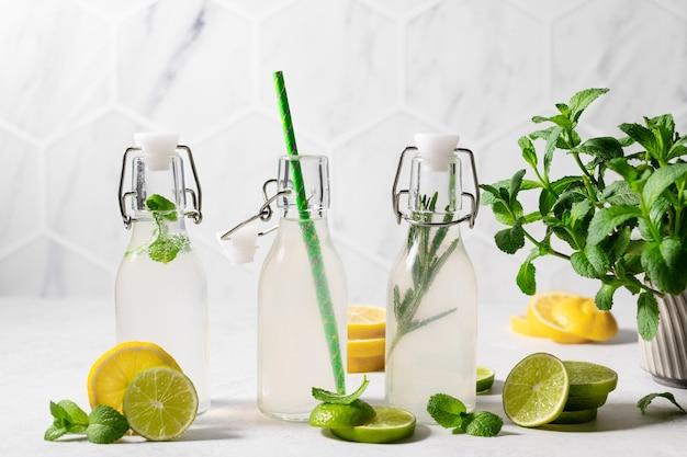 Drie flesjes limonade met limoen citroen munt rozemarijn zomerdrankje