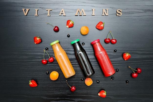 Drie flessen met sap, fruit en inscriptie vitaminen op een donkere houten tafel, voedsel concept