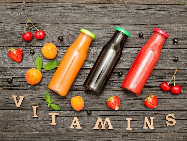Drie flessen met sap, fruit en inscriptie vitamines op een houten achtergrond