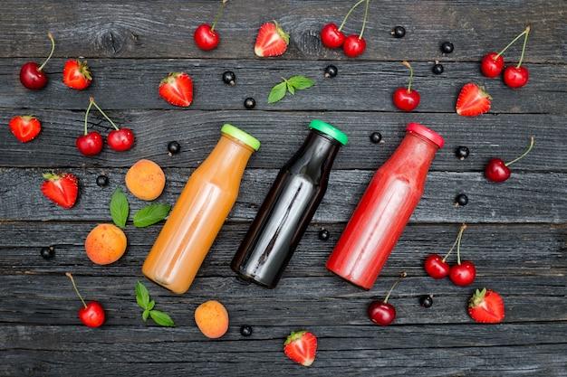 Drie flessen sap en fruit op zwarte houten tafel. voedsel concept
