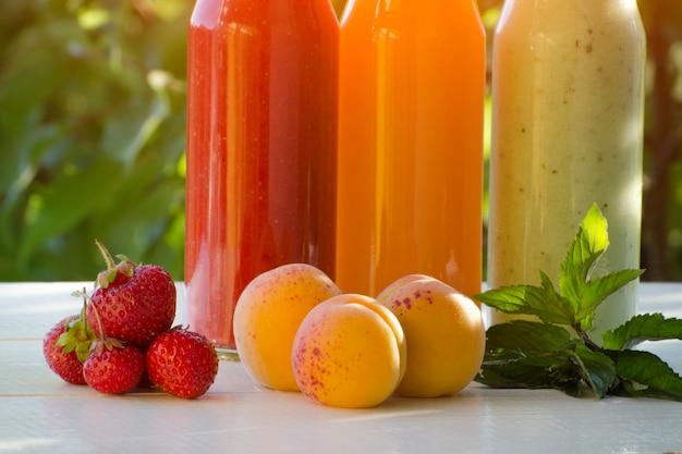 Drie flessen sap met fruit. zomer, zonlicht. detailopname