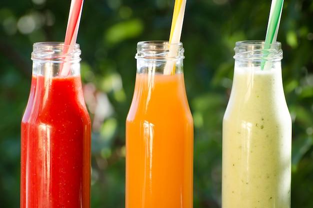Drie flessen sap met rietjes, zomer, zonlicht. detailopname