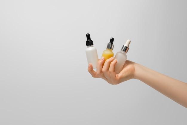 Drie flessen serum in de hand van een vrouw op een lichte achtergrond.