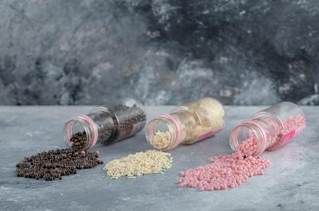 Drie flessen snoep en hagelslag op marmeren tafel.