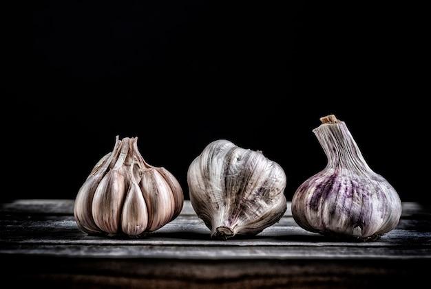 Drie garlics in verschillende positie op een houten bord op zwarte achtergrond
