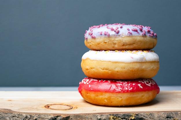 Drie geassorteerde geglazuurde donuts van verschillende kleuren op een houten plank op een grijze achtergrond.