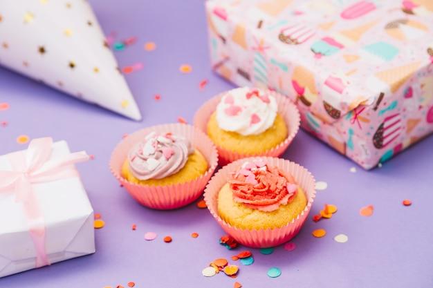 Drie gebakken muffins met cadeautjes; feestmuts en confetti op paarse achtergrond