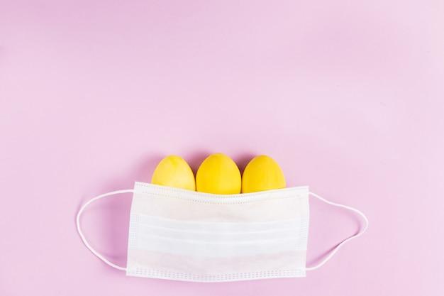 Drie geel gekleurde paaseieren met een beschermend gezichtsmasker op een roze achtergrond