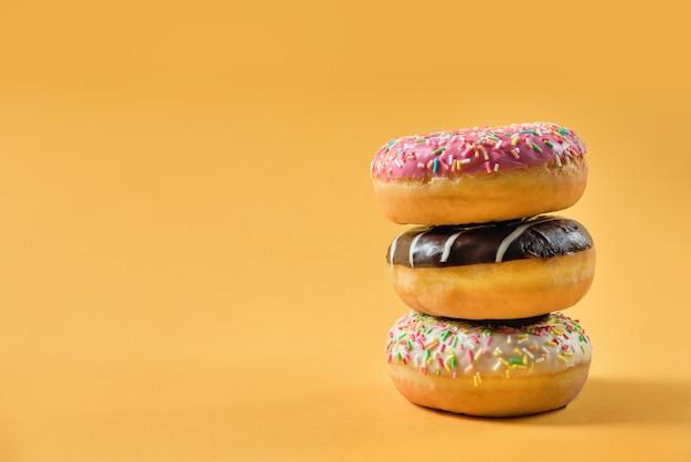 Drie geglazuurde donuts op een gele achtergrond met kopie ruimte.