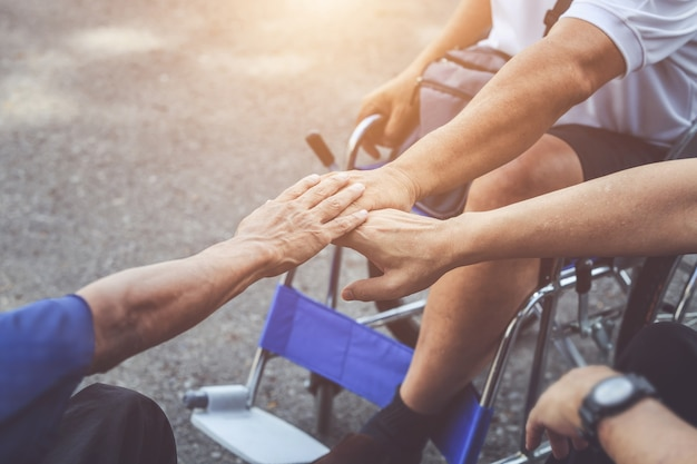 Drie gehandicapte mensen die op rolstoel zitten en hun hand samenstellen