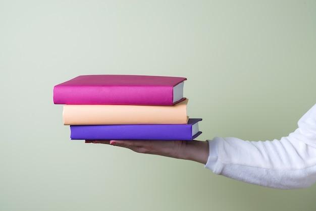 Drie gekleurde boeken op een hand