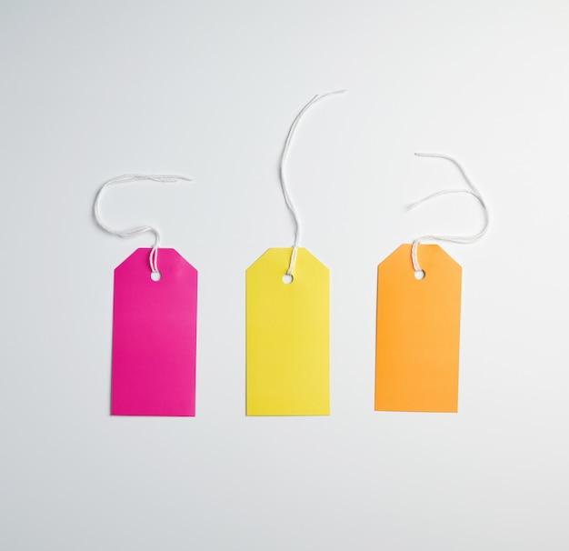 Drie gekleurde papieren labels aan een wit touw