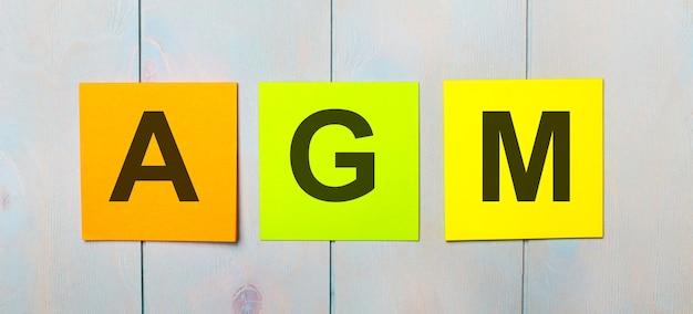 Drie gekleurde stickers met de tekst agm annual general meeting op een lichtblauwe houten achtergrond