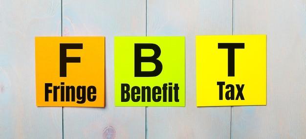 Drie gekleurde stickers met de tekst fbt fringe benefit tax op een lichtblauwe houten ondergrond